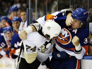 Penguins' McKee fights with the Islanders' Witt during the first period of their NHL hockey game in Uniondale